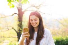 Lächelnde Jugendliche mit Handy Stockbild