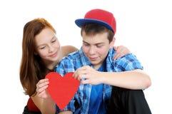 Lächelnde Jugendliche und Junge, die einen Valentinsgruß herausgeschnitten vom roten Papier mit Scheren anhält stockfotos