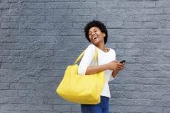 Lächelnde junge afrikanische Frau mit dem Handy, der weg schaut Lizenzfreies Stockfoto