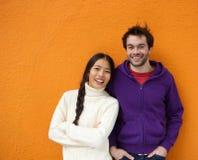 Lächelnde junge asiatische Frau, die nahe bei glücklichem jungem Mann steht Stockbild