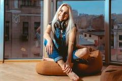 Lächelnde junge blonde Aufstellung des Spaßes auf Couch und Betrachten von Kamerane Stockfotos