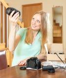 Lächelnde junge blonde auspackende neue Digitalkamera und Ziele Lizenzfreie Stockbilder
