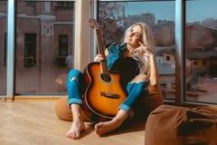 Lächelnde junge blonde Dame mit Gitarre in ihren Händen, die Ca betrachten Lizenzfreies Stockfoto