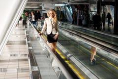 Lächelnde junge blonde Frau, die auf beweglichen Gehwegen im Büro steht Stockfotos