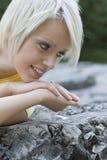 Lächelnde junge blonde Frau, die auf einem Felsen liegt Lizenzfreies Stockbild