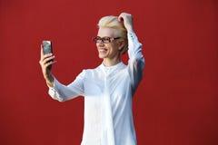 Lächelnde junge blonde Frau, die selfie nimmt Lizenzfreies Stockbild