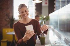 Lächelnde junge blonde Frau, die Smartphone beim Sitzen mit Getränk am Zähler verwendet Stockbild