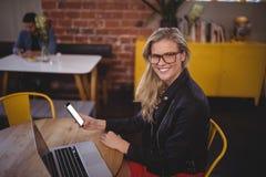Lächelnde junge blonde Frau, die Smartphone beim Sitzen mit Laptop an der Kaffeestube hält Stockfoto