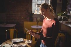 Lächelnde junge blonde Frau, die Smartphone an der Kaffeestube verwendet Lizenzfreie Stockfotos