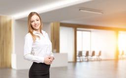 Lächelnde junge blonde Frau im Büroflur Lizenzfreies Stockbild