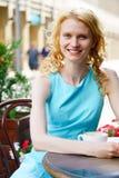 Lächelnde junge blonde Frau im Café mit Schale Cappuccino Stockbild