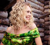 Lächelnde junge blonde Frau im grünen Kleid Stockfoto