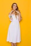 Lächelnde junge blonde Frau im weißen Kleid auf gelbem Hintergrund Lizenzfreie Stockfotografie