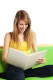 Lächelnde junge blonde Frau mit Buch Lizenzfreie Stockfotos