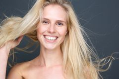 Lächelnde junge blonde Frau mit dem Schlaghaar Stockbilder