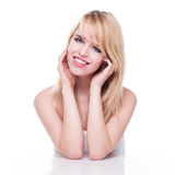 Lächelnde junge blonde Frau mit Kopf in den Händen Lizenzfreie Stockbilder