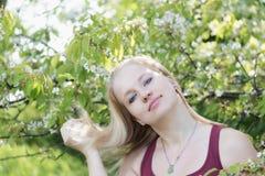Lächelnde junge blonde Frau spielt mit ihrem Haar Stockfotos