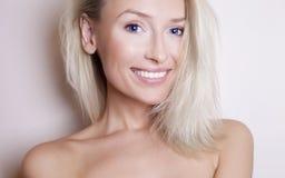 Lächelnde junge blonde Schönheit mit blauen Augen. Stockfotografie