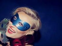 Lächelnde junge blonde Schönheit mit Karnevalsmasken Stockbild