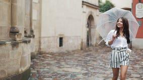 Lächelnde junge brunette Frau in den Kleiderwegen mit Regenschirm entlang der Straße einer alten Stadt Gehen unter den Regen stock footage
