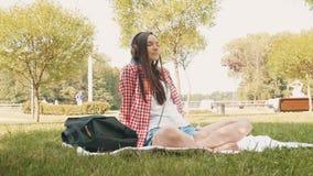 Lächelnde junge Brunettefrau, die Musik beim Sitzen auf Gras im Park hört stock video footage