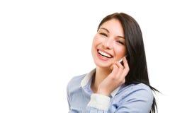 Lächelnde junge Brunettefrau, die am Telefon spricht Stockfotos