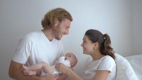 Lächelnde junge Elternfrau mit dem Mann, der wenig Baby in den Armen und zu Hause genießen hält stock video footage