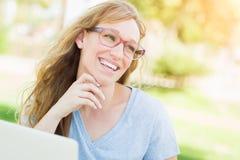 Lächelnde junge erwachsene Frauen-tragende Gläser draußen unter Verwendung ihres Laptops Stockfotografie