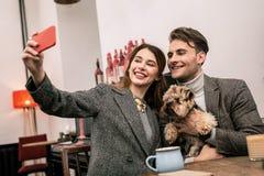 Lächelnde junge Familie, die selfie mit ihrem Haustier macht stockfotografie