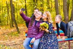 Lächelnde junge Familie, die selfies an einem Herbsttag nimmt lizenzfreies stockfoto