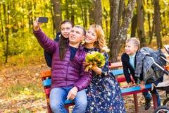 Lächelnde junge Familie, die selfies an einem Herbsttag nimmt stockbild