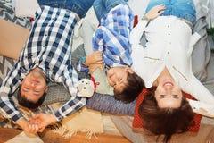 Lächelnde junge Familie mit dem Sohn, der Kamera während Lügentoge betrachtet lizenzfreies stockbild