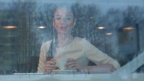 Lächelnde junge Frau am Café mit Kopfhörern hörend Musik von der Tablette stock footage
