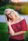 Lächelnde junge Frau in den Gläsern mit dem Telefon draußen Stockbild