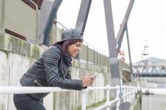 Lächelnde junge Frau der Mode, die intelligentes Telefon in der Straße verwendet Stockfotografie