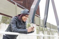 Lächelnde junge Frau der Mode, die intelligentes Telefon in der Straße verwendet Stockfoto