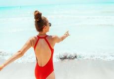 Lächelnde junge Frau in der roten Strandkleidung auf dem Strand, der Spaßzeit hat lizenzfreies stockbild