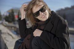Lächelnde junge Frau in der Sonnenbrille schwarzer Mantel und Schal weit lächelnd mit den Zähnen und von der Sonne schielend lizenzfreie stockfotos