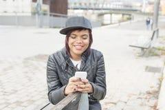 Lächelnde junge Frau, die auf Bank und der Anwendung des intelligenten Telefons sitzt Stockfotos