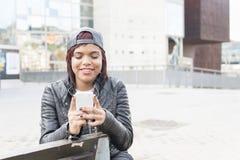 Lächelnde junge Frau, die auf Bank und der Anwendung des intelligenten Telefons sitzt Lizenzfreie Stockfotografie