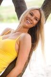 Lächelnde junge Frau, die auf Baum-Zweig sich lehnt Stockfotografie