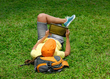 Lächelnde junge Frau, die auf dem Rasen mit einem Tablet-Computer liegt Stockbild