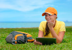 Lächelnde junge Frau, die auf dem Rasen mit Rucksack und Tablette c liegt Stockfoto