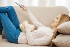 Lächelnde junge Frau, die auf dem Sofa liegt Lizenzfreies Stockbild