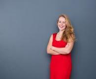 Lächelnde junge Frau, die auf grauem Hintergrund steht Stockfotografie