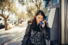 Lächelnde junge Frau, die auf ihrem Smartphone auf der Straße spricht Verständigend mit Freunden, geben Sie Anrufe und Mitteilung lizenzfreie stockfotos