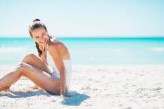 Lächelnde junge Frau, die auf Strand sitzt und auf Kopienraum schaut Lizenzfreie Stockbilder