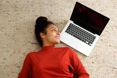 Lächelnde junge Frau, die auf Teppich mit Laptop liegt stockbilder