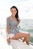 Lächelnde junge Frau, die auf Yachtplattform sitzt Stockfotos