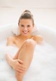 Lächelnde junge Frau, die in der Badewanne sich entspannt Lizenzfreies Stockbild